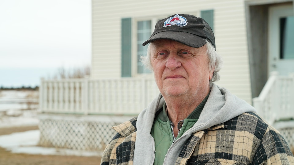 Brian Josey, propriétaire du restaurant de l'Île d'Entrée avec une casquette noir et son manteau devant une maison au centre de la communauté.