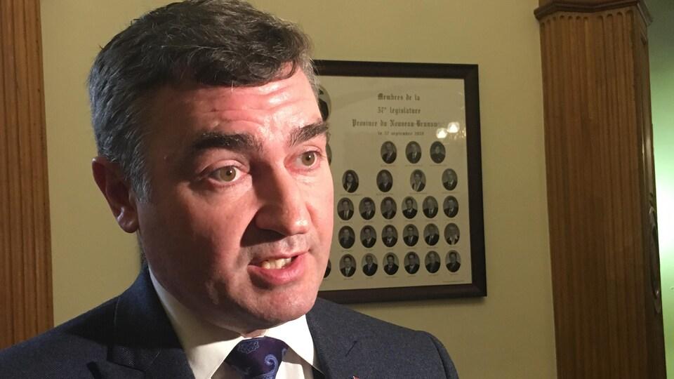 Le député MacDonald s'adresse aux journalistes dans le hall de l'Assemblée législative.
