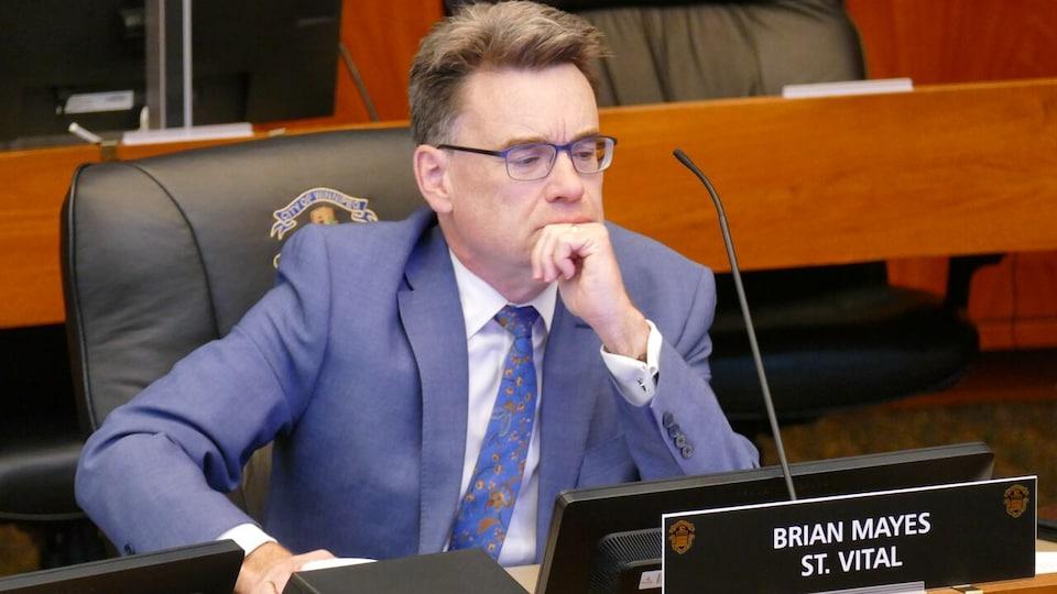 Brian Mayes au conseil municipal, l'air soucieux.