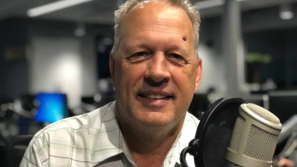 Un homme devant un microphone.