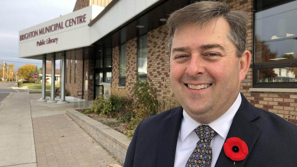 Le maire de Brighton habillé en complet-cravate, sourit devant l'hôtel de ville.