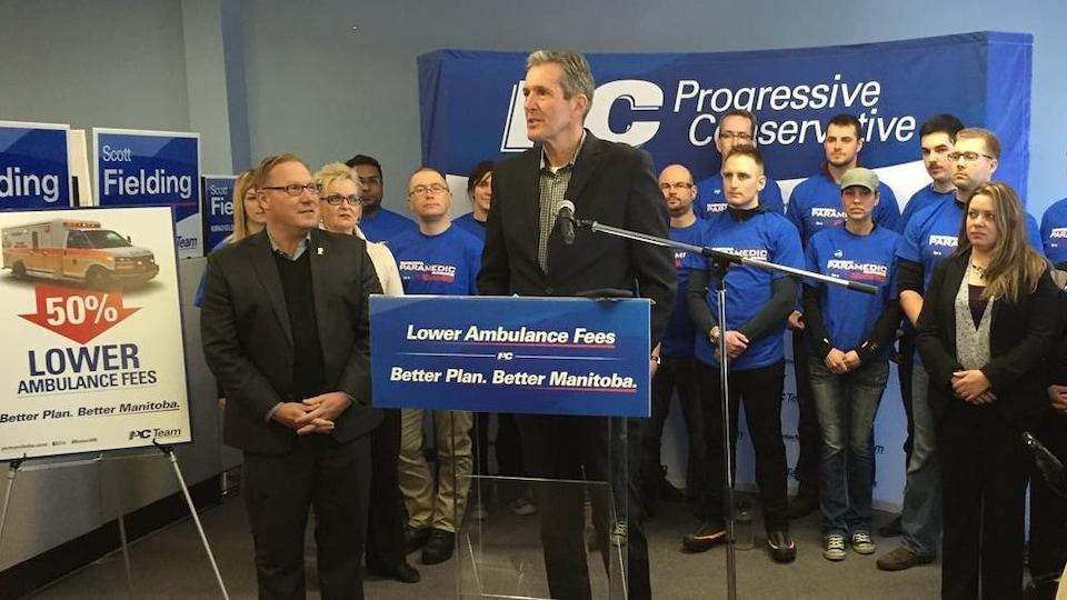 Photo d'archives du chef progressiste-conservateur Brian Pallister en 2016, entouré de candidats de son parti, devant un podium bleu qui dit, en anglais : « Réduire les frais d'ambulance, un meilleur plan pour un meilleur Manitoba ».