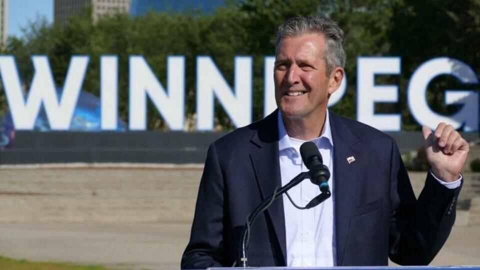 Un homme parle à un micro. En arrière-plan, le grand panneau de la ville de Winnipeg sur lequel on peut lire : Winnipeg