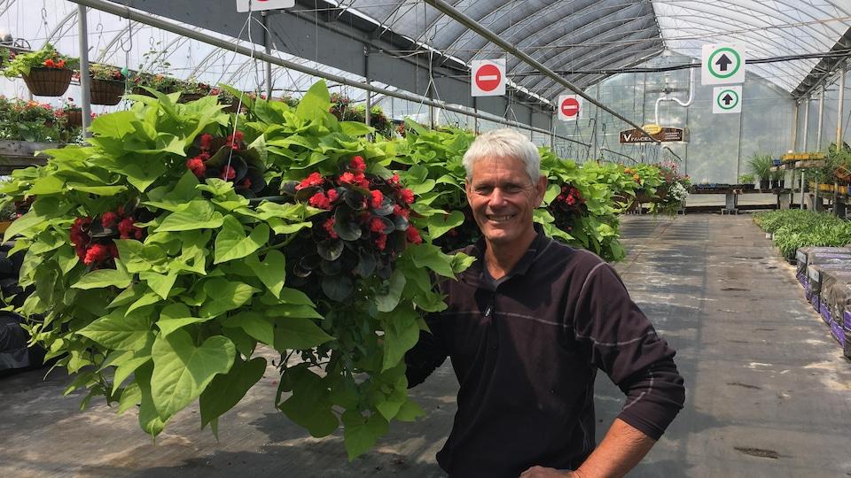 Brian Scullion est à côté d'une plante suspendue.