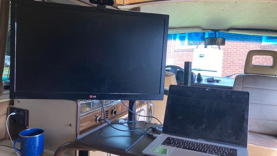 Un ordinateur portable sur une tablette mobile fixée à une armoire.