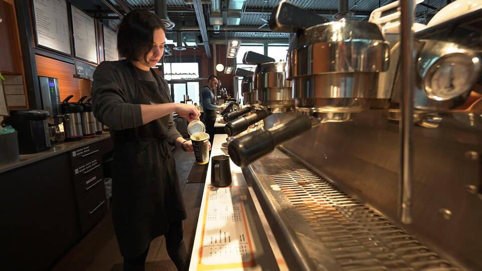 Une femme à l'intérieur d'un café, derrière un comptoir et devant des machines à espresso.
