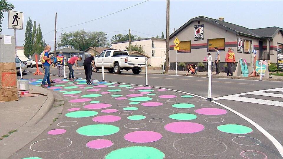 Des ronds de peinture sont dessinés sur une intersection. Des gens en veste de construction se tiennent de part et d'autre de la route.