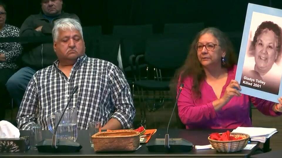Une femme autochtone témoigne lors d'une commission d'enquête en tenant une affiche où est écrit : « Gladys Tolley killed 2001 ».