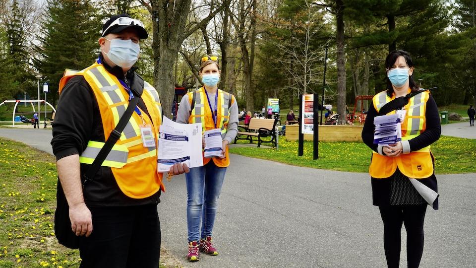 Trois personnes portant des dossards orange tiennent des dépliants d'information sur la COVID-19 dans leurs mains.