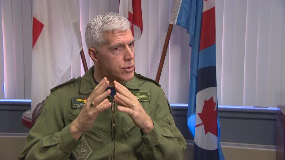Un officier des Forces armées canadiennes en combinaison de vol pose devant des drapeaux dans son bureau.