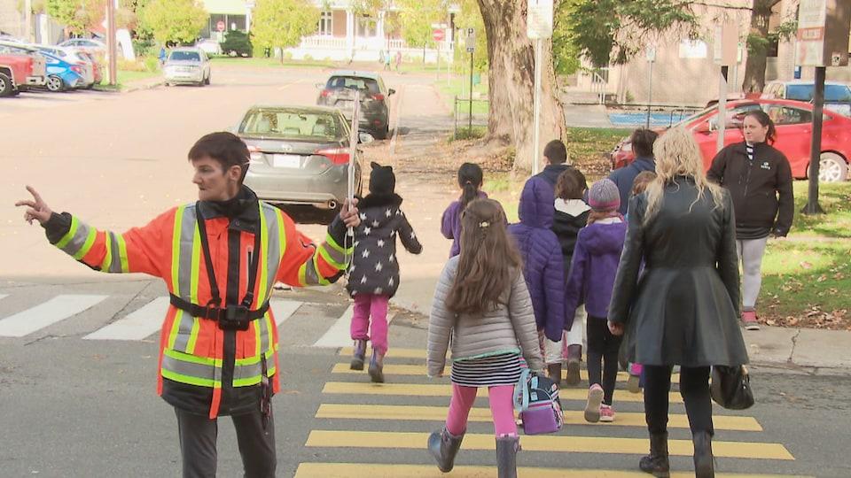 Une brigadière fait signe à un véhicule de s'arrêter pendant qu'un groupe d'enfants traverse la rue.