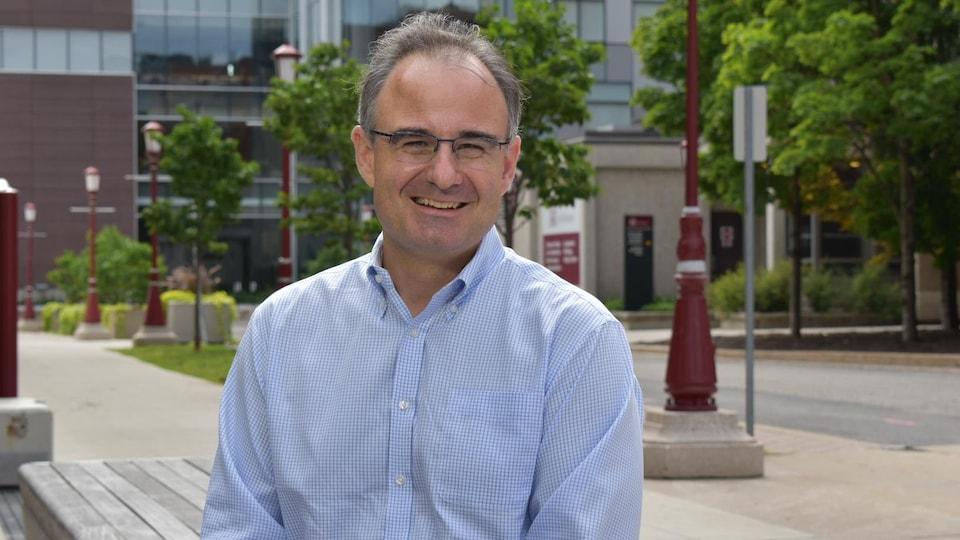 Patrick Leblond pose pour la caméra sur la campus de l'Université d'Ottawa en été.