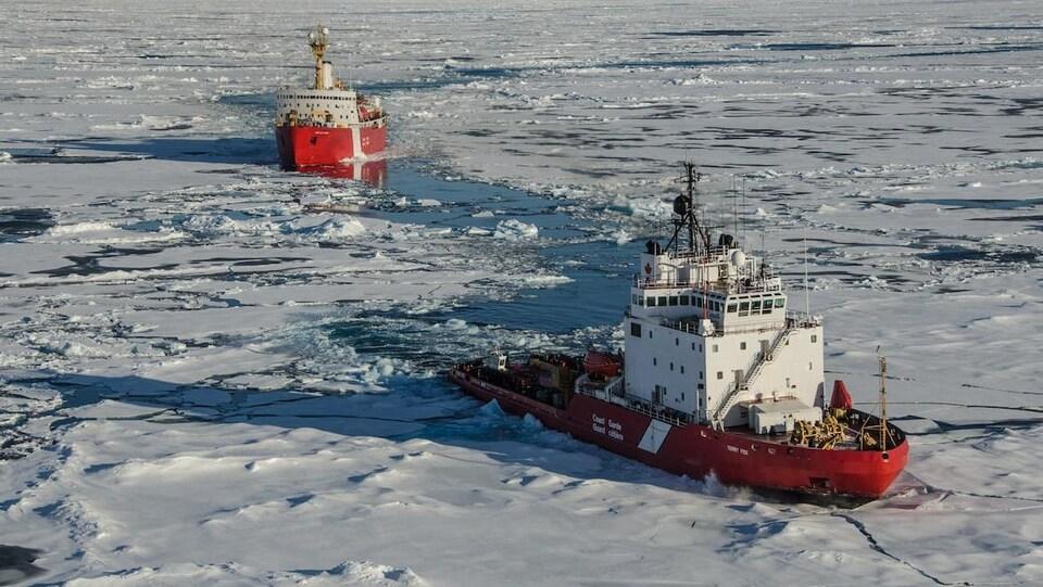 Des navires de la Garde côtière naviguent sur des eaux partiellement recouvertes de glaces.