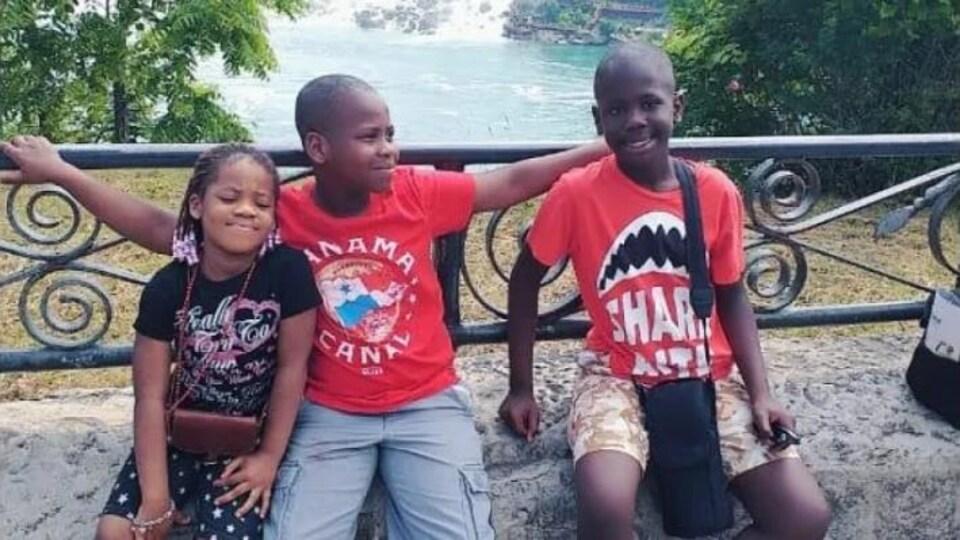 Une fille et deux garçons assis.