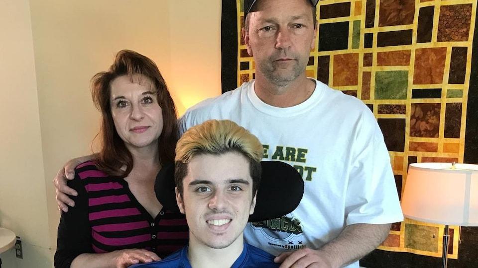 Vue sur une mère, père et un jeune homme dans un fauteuil roulant.