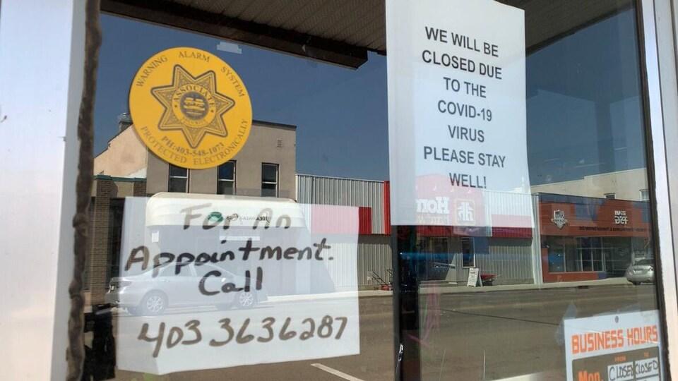 Des affiches sur une vitrine informent les clients de la fermeture d'un commerce en raison de la COVID-19.