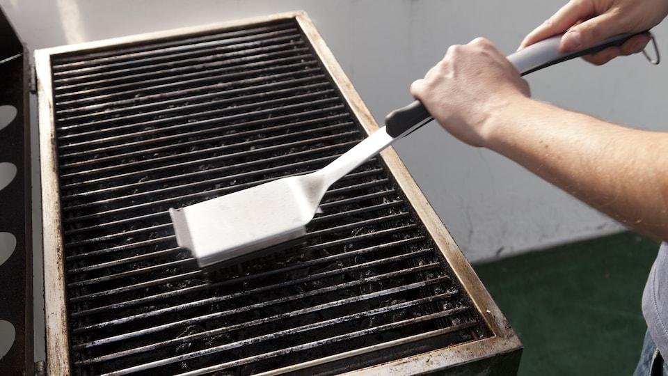 Une personne nettoie les grilles d'un barbecue à l'aide d'une brosse métallique.