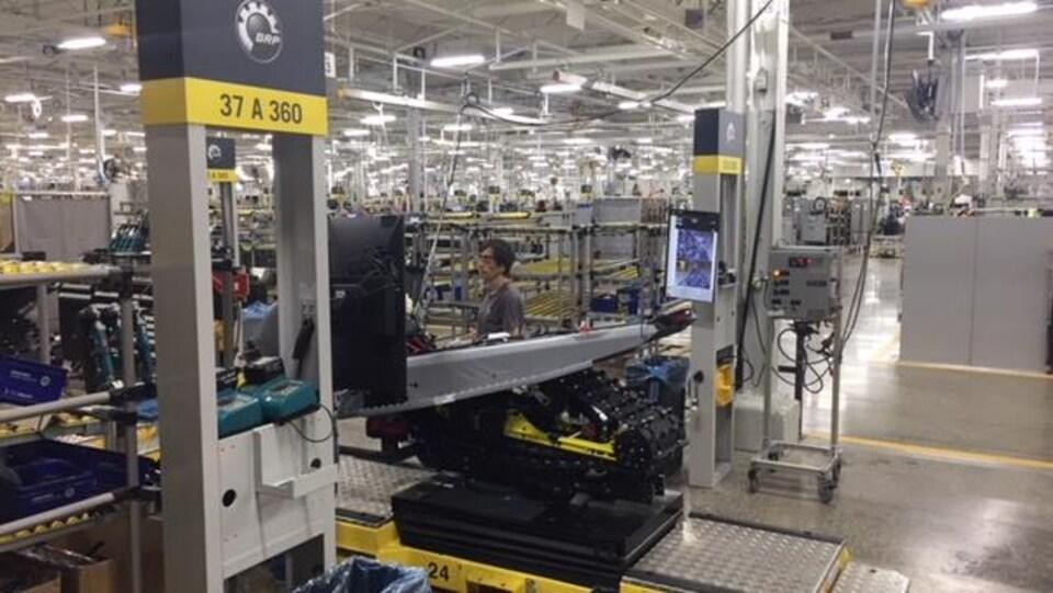 Un travailleur près d'une machine dans la nouvelle usine de fabrication de motoneiges Ski-Doo et de véhicules Can-Am Spyder modernisée.