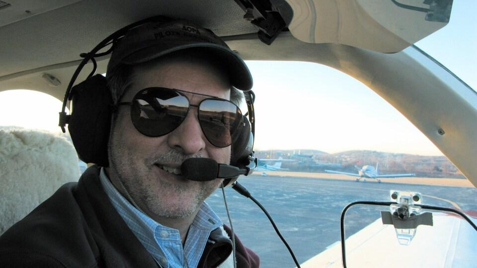 Un homme sourit à la caméra dans un petit avion, casque d'écoute sur la tête.