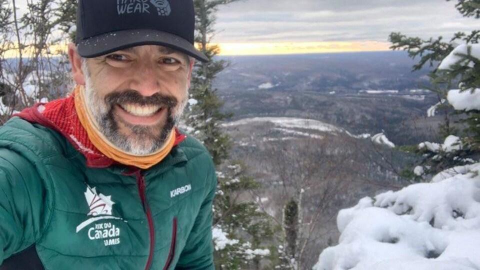 Bruce Guitard souriant entouré de neige.