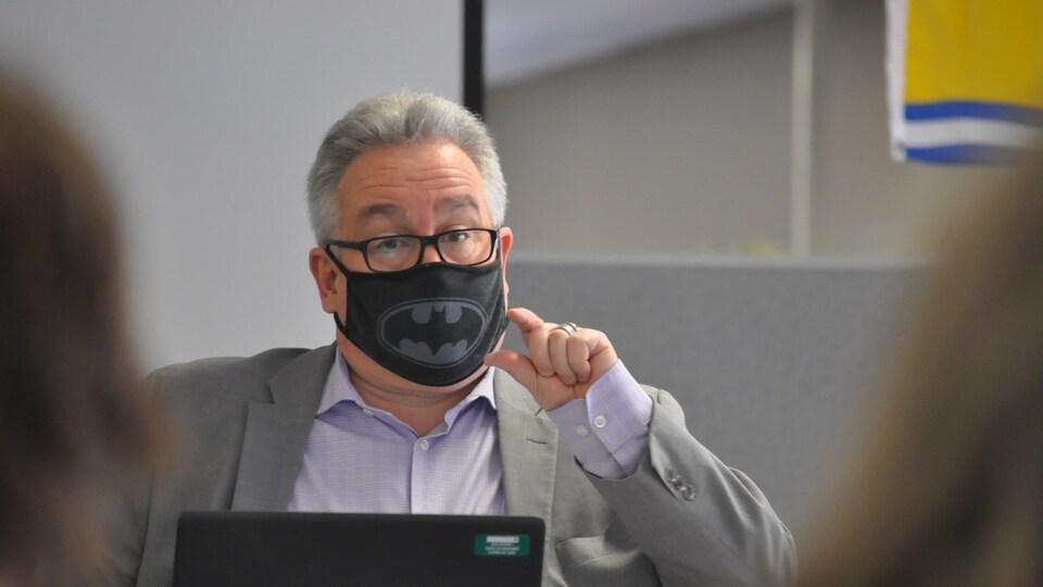 Bruce Macfarlane assis devant un ordinateur portable durant une réunion. Il porte un masque décoré du logo de Batman.