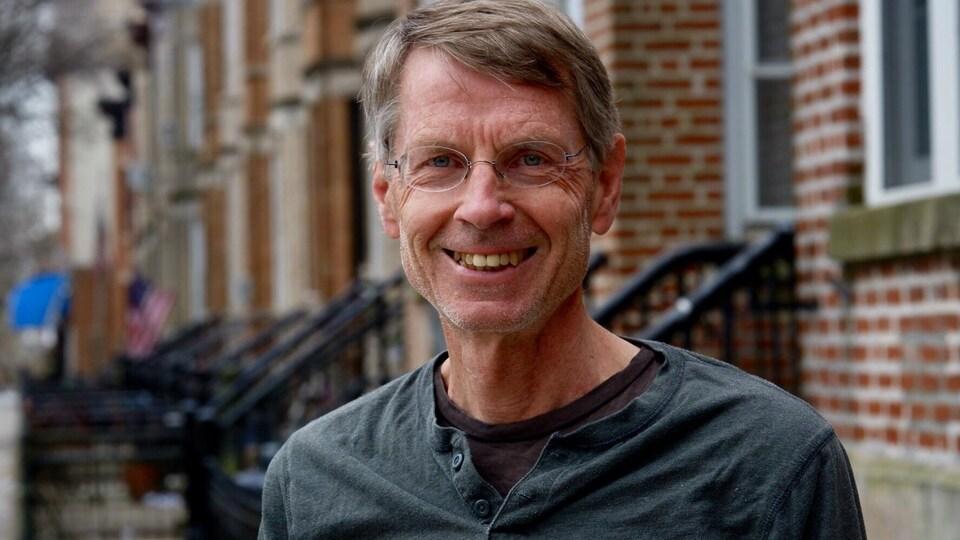 Un homme aux cheveux gris et portant des lunettes est posé devant un immeuble de briques rouges.