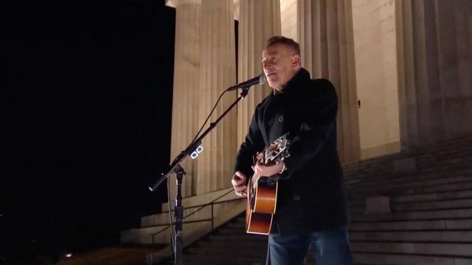 Bruce Springsteen chante et joue de la guitare dehors devant de grosses colonnes de pierre.