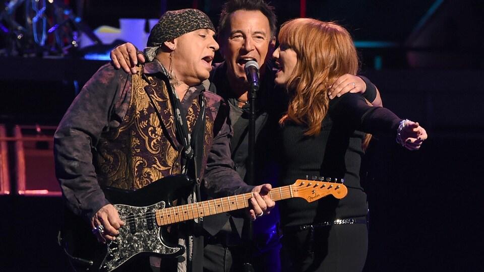 Les trois artistes chantent dans le même micro.
