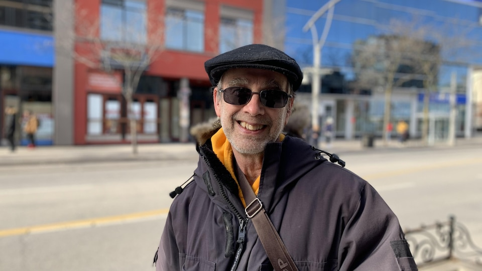 Portrait d'un homme souriant dans une rue. Il porte un casquette et des lunettes fumées