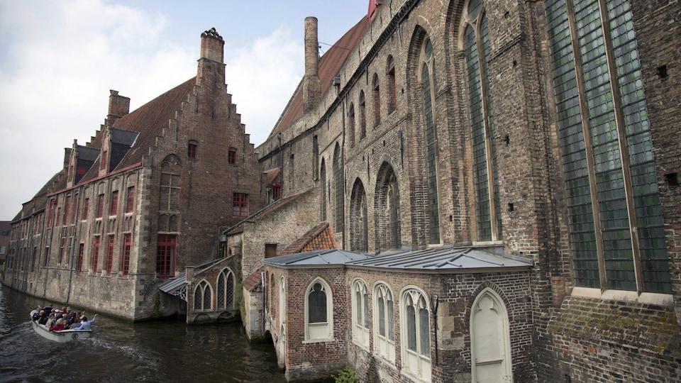 Des touristes dans un bateau d'un canal d'une vieille ville.