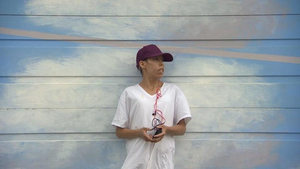 Une femme debout devant un mur.