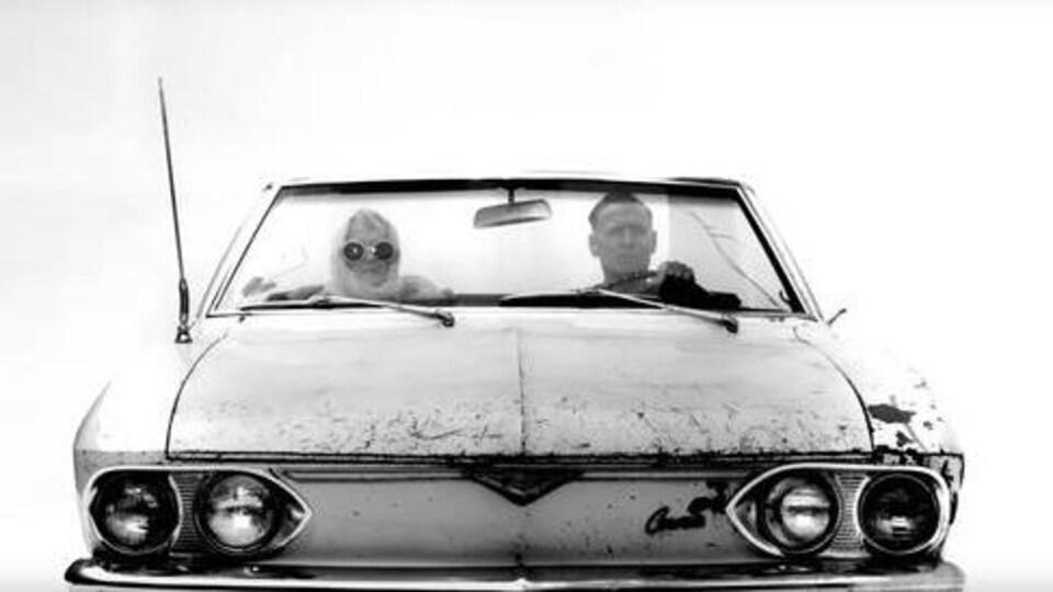 Une homme conduit une voiture décapotable.