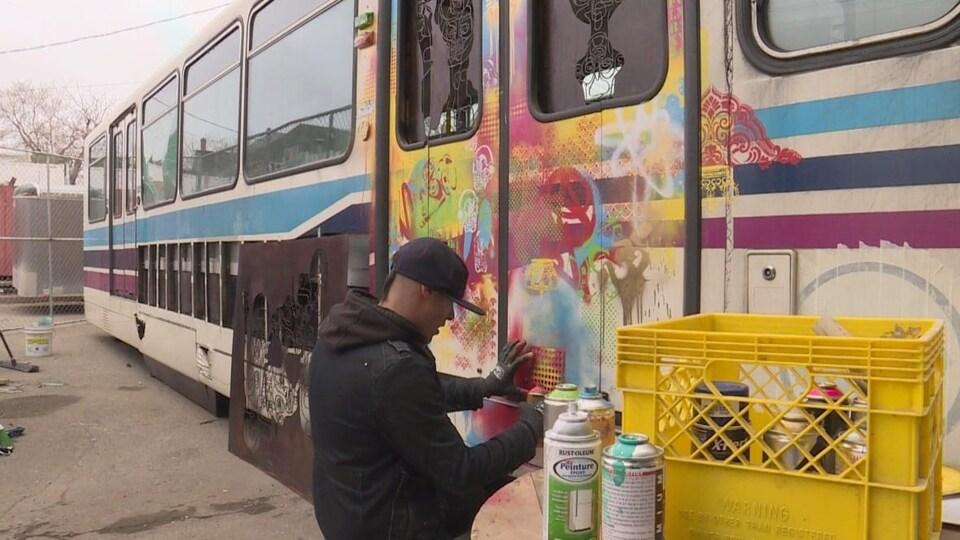Bryan Faubert est en train de peindre avec une canette de peinture en aérosol et un pochoir sur la porte extérieure de la voiture du train léger.