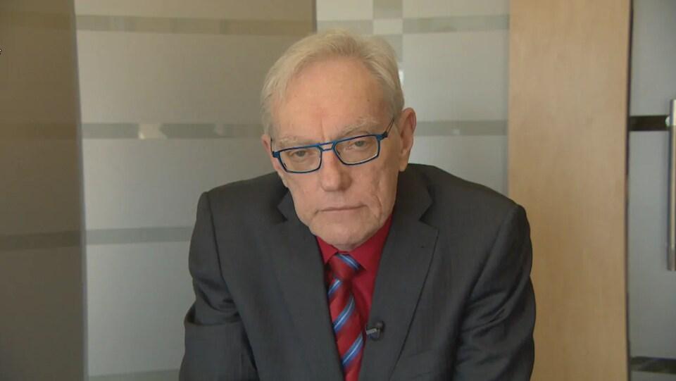 Un homme âgé en complet regarde la caméra, sans sourire. Il porte des lunettes.