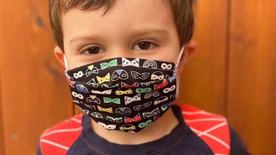 Un garçon porte un masque de protection.