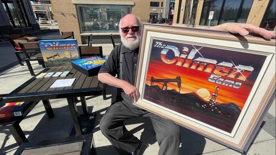 Un homme avec une barbe et des lunettes est assis et tient un tableau avec une gravure du jeu The Oilman game.