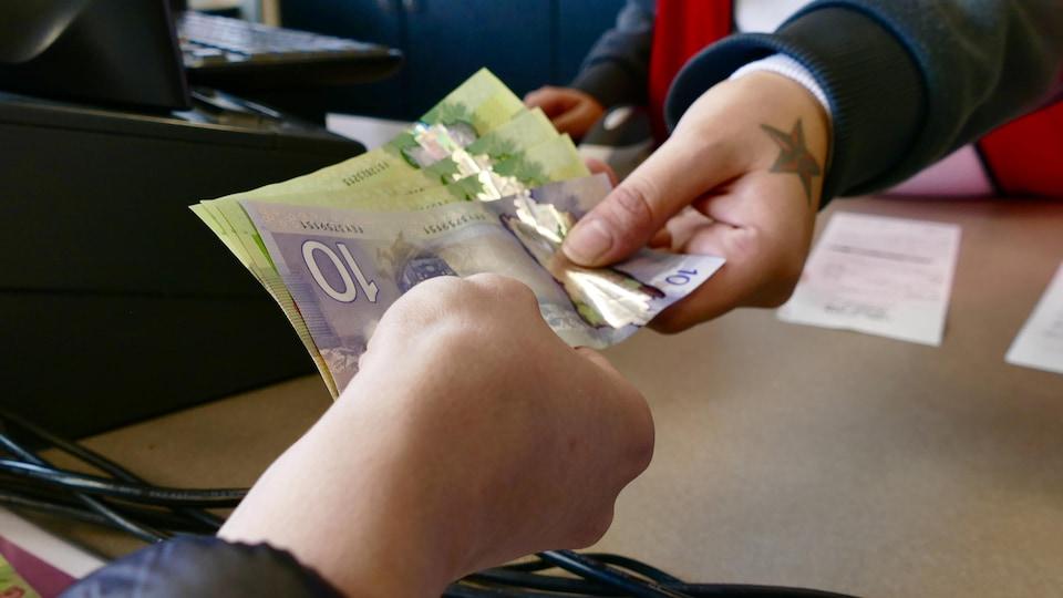 Des mains échangent des coupures de 10 $ et de 20 $.