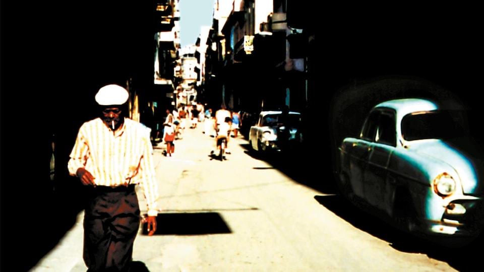 Un homme avec un chapeau blanc marche dans les rues de La Havane.