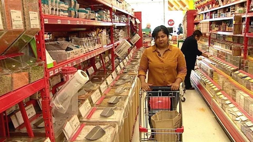 Une femme pousse un chariot dans une allée dans un magasin.
