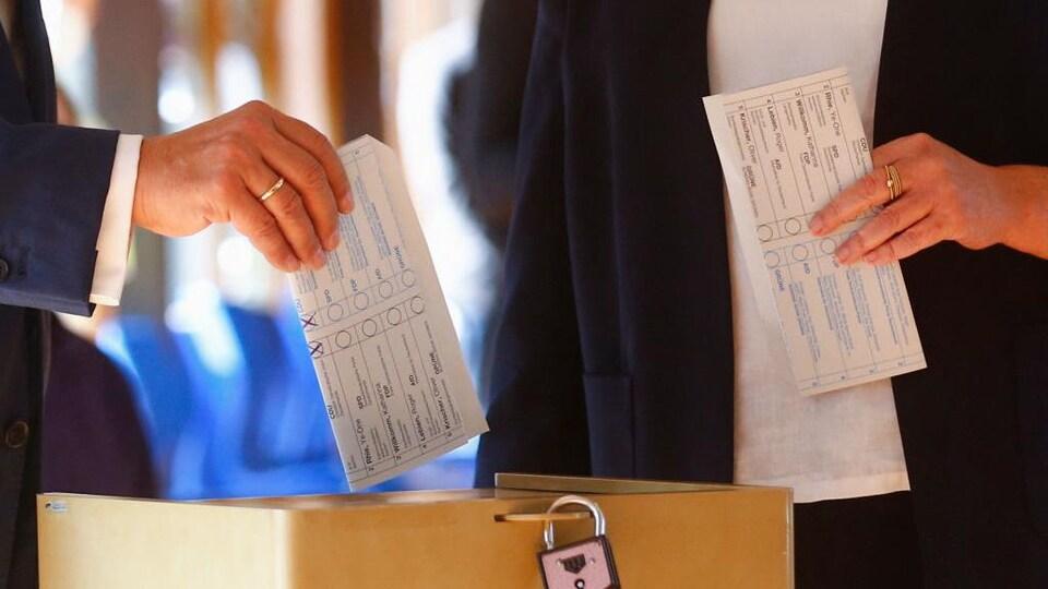 Une main tient un bulletin de vote sur lequel on peut voir deux « X » tracés au crayon.