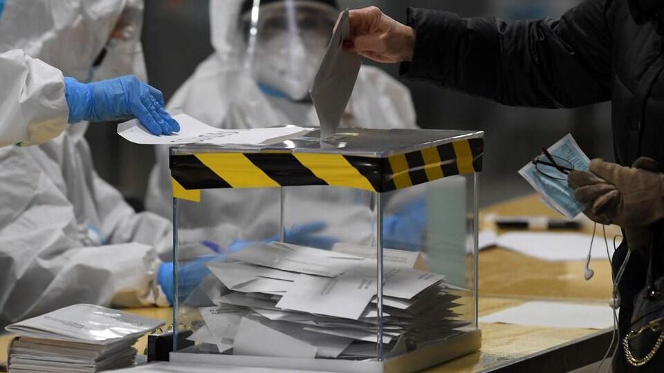 Des personnes vêtues de combinaisons intégrales, de masques, de visière et de lunettes de protection regardent une personne mettre son bulletin de vote dans l'urne.