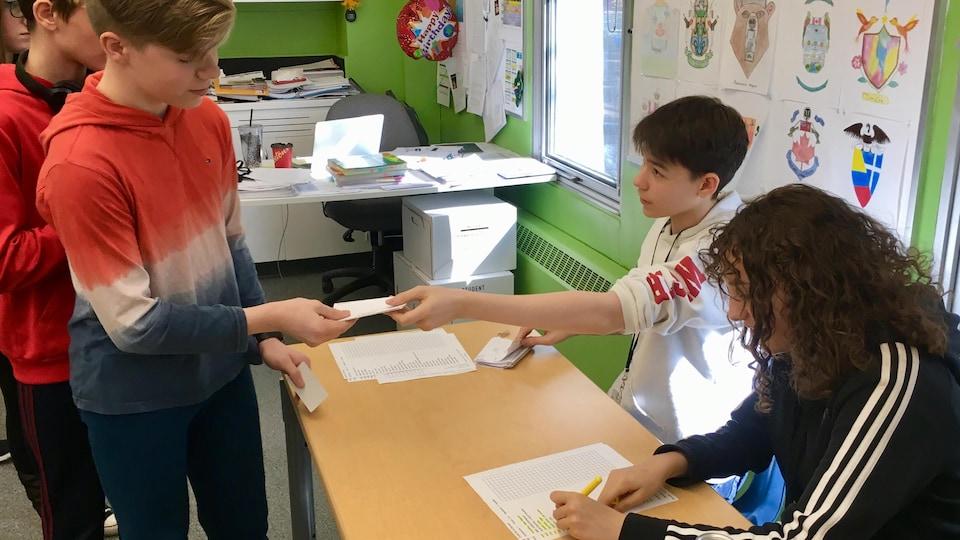 Deux jeunes sont assis derrière une table. Alors que la première surligne une liste sur une feuille, le second tend un papier à un troisième jeune, debout de l'autre côté de la table.