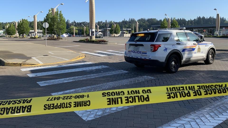 Un véhicule de police dans un stationnement de centre commercial.