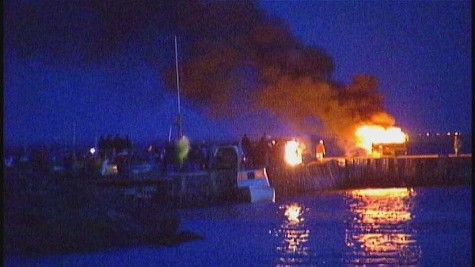 Un bateau en feu sur un quai, le soir.
