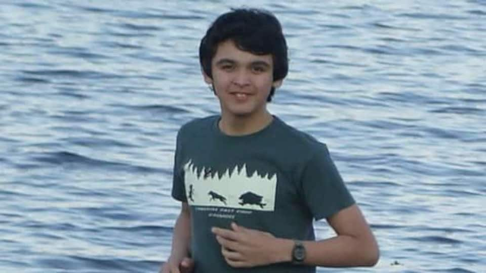 Un adolescent en t-shirt sur le bord de l'eau en été.