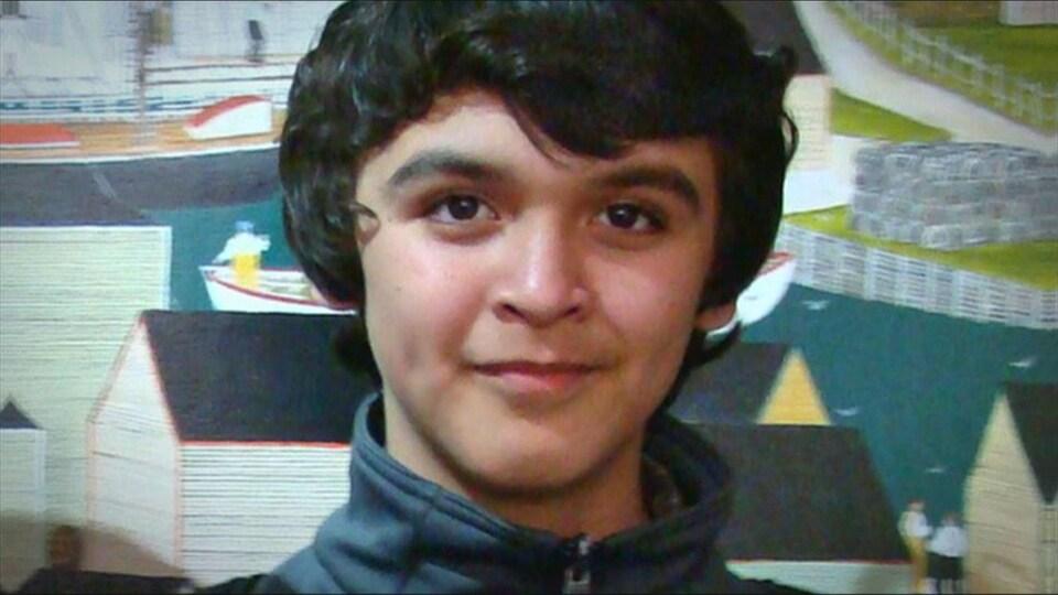 Un adolescent fixe la caméra dans ce qui semble être une photo prise à l'école.