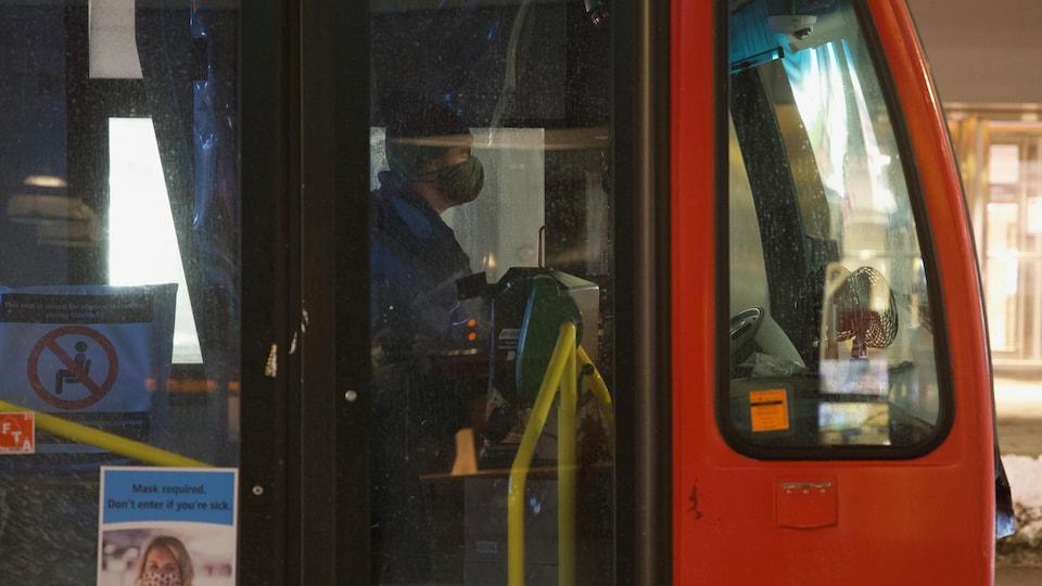 Le chauffeur masqué derrière les portes de son autobus.