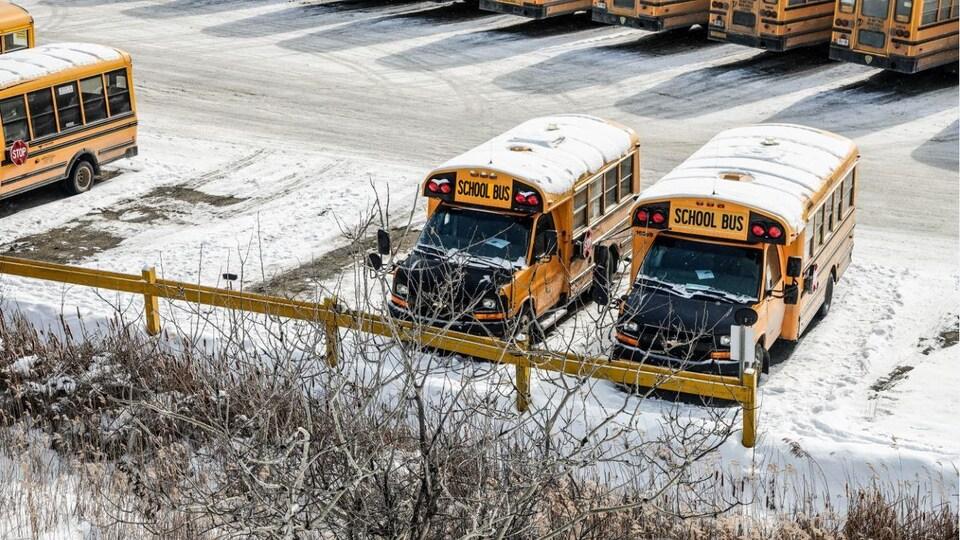Des bus dans un stationnement enneigé.