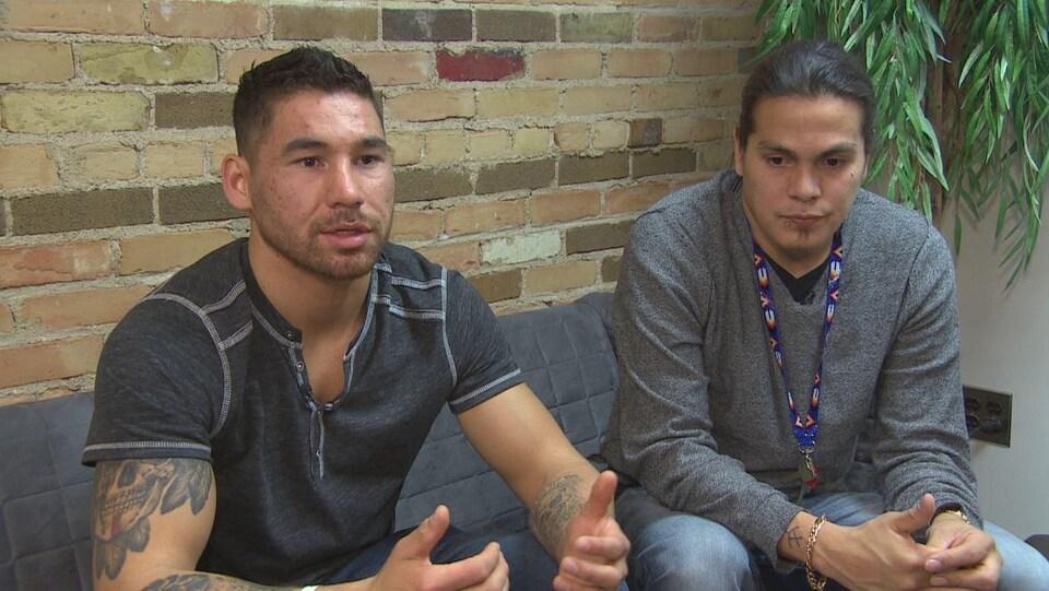 Deux jeunes hommes sont assis sur un fauteuil. Celui de gauche a les cheveux courts noirs et parle en levant les mains. Celui de droite avec de longs cheveux bruns l'écoute, le regard tourné vers le bas, dans le vague.
