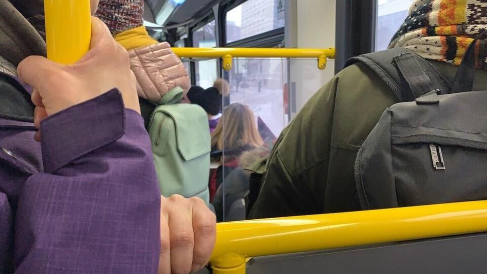 Des mains agrippent des barres à l'intérieur d'un autobus bondé.